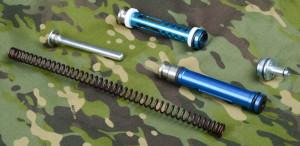 Kuvassa AirsoftPron jousi, jousenohjain, mäntä ja sylinterinpää sekä ylimpänä Action Armyn mäntä.